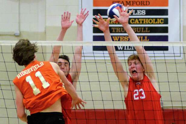 Ridgefield's Andrew Knachel (11) spikes the ball past Fairfield Warde's Luke Adelstein (23), at right, during boys volleyball action in Fairfield, Conn., on Wednesday Apr. 25, 2018. Attempting to block with Adelstein is teammate Luke Connor (3).