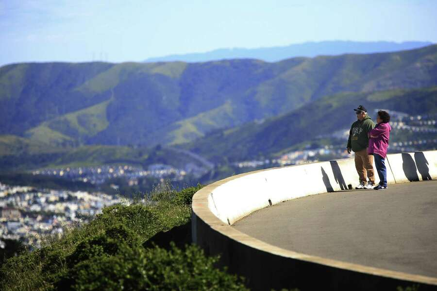Serf Rodriquez (left) and Maggie Rodriguez of Seattle take in the view from atop Twin Peaks while enjoying a walk along the half of the figure-eight road that will remained closed to motorized vehicle. Photo: Lea Suzuki / The Chronicle / ONLINE_YES