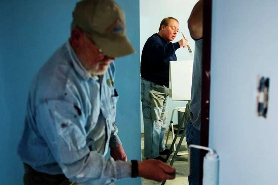 Midland residents Betsy Evans, center, and Eldon Enger, left, work to paint the walls of a bedroom on Wednesday, April 18. Volunteers from Trinity Lutheran worked over a two-week period to repair three Midland homes from damage sustained in the historic June 2017 flooding. (Katy Kildee/kkildee@mdn.net)