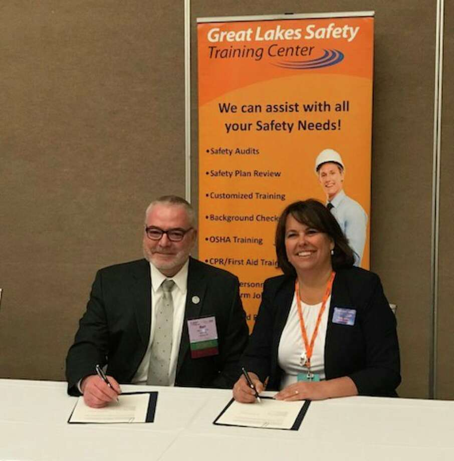 Bart Pickelman, Michigan Occupational Safety and Health Administration director, and Kelly Juday, Great Lakes Safety Training Center executive director, sign an alliance agreement formalizing a mutual commitment to workplace safety and health. (Photo provided)
