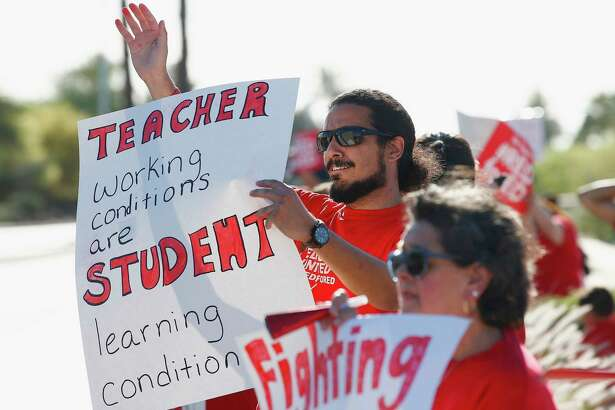 Teachers, parents and students line up along a local street waving to passing vehicles for the latest teacher protest for higher teacher pay and school funding Wednesday, April 25, 2018, in Phoenix. Teachers are scheduled to go on strike Thursday.
