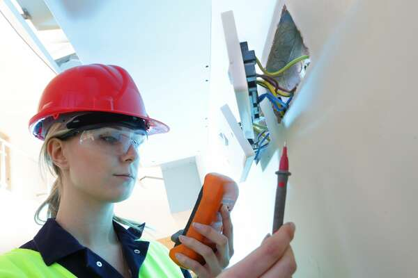 female electrician checking sockets