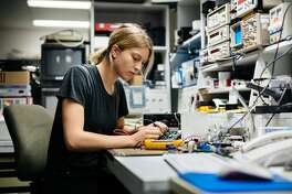 Young female engineer measuring voltage on a  conductor board in her workshop