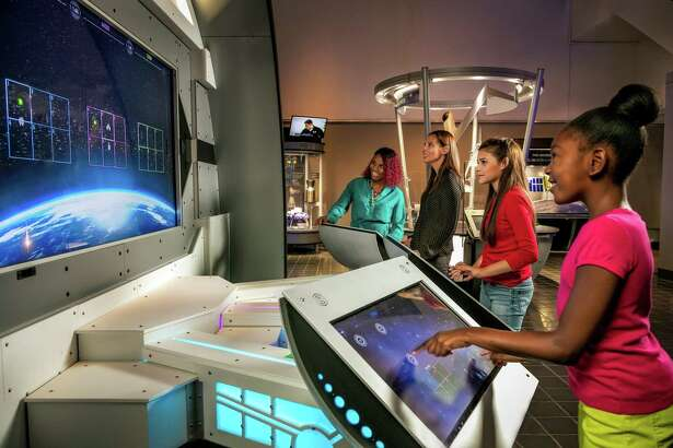"""Families interact with the """"Above and Beyond"""" exhibit at Space Center Houston."""