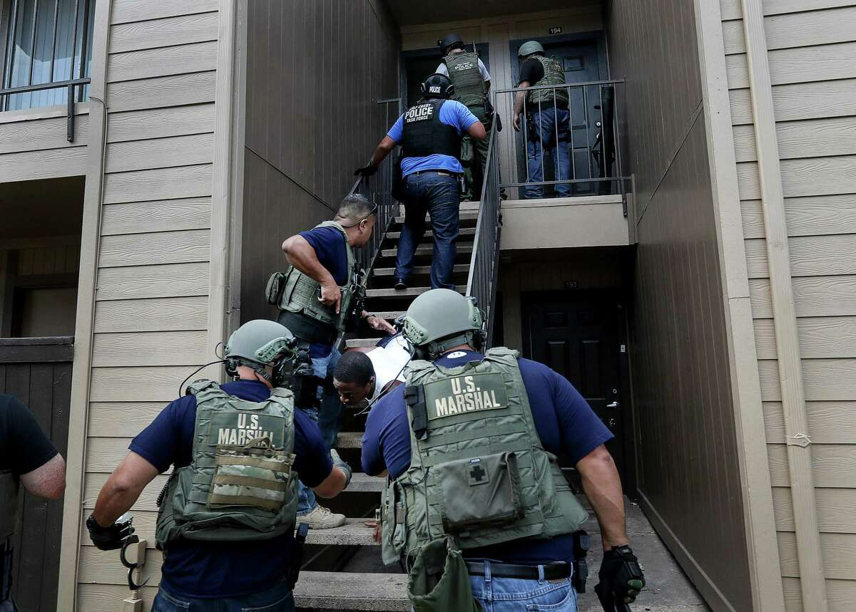 Members of the Gulf Coast Violent Offenders Task Force raid an apartment in north Houston to apprehend a man who is wanted for murder, Wednesday, July 26, 2017, in Houston. The team received a tip that he was hiding in the complex, and they prepared in a nearby parking lot. Assistant Deputy U.S. Marshal Leslie Ramin was pulled from another investigation to help serve the search warrant. ( Jon Shapley / Houston Chronicle )