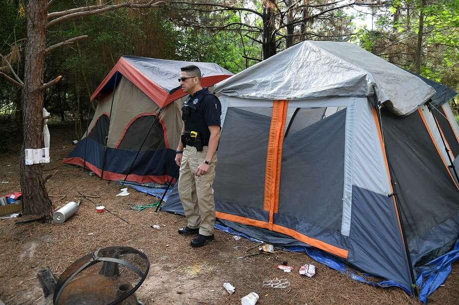 Deputy Luke Ditta, of the Harris County Sheriff's Office Homeless Outreach Team, takes a walk-around at the wooded encampment near W. FM 1960 and Nanes Dr. in Houston on April 12, 2018. (Photo by Jerry Baker/Freelance) Photo: Jerry Baker, Freelance / For The Chronicle / Freelance