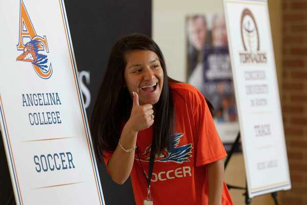Bety Hernandez gives a thumbs-up as she poses next to a poster for her before a signing ceremony at Porter High School, Thursday, April 26, 2018. Hernandez signed to play soccer for Angelina College.