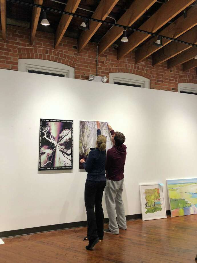 "Afsaneh Djabbari-Aslani (left) and Mark Macrides hang photographs by Joanie Landau and Mary Ellen Hendricks Wednesday night in preparation for Friday's opening of the Loft Artists Association's ""Bring a Friend to the LAA"" exhibit. Photo: /"