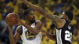 Golden State Warriors' Kevin Durant, left, looks to pass away from San Antonio Spurs' Rudy Gay (22) during the fourth quarter in Game 5 of a first-round NBA basketball playoff series Tuesday, April 24, 2018, in Oakland, Calif. Golden State won 99-91. (AP Photo/Ben Margot)