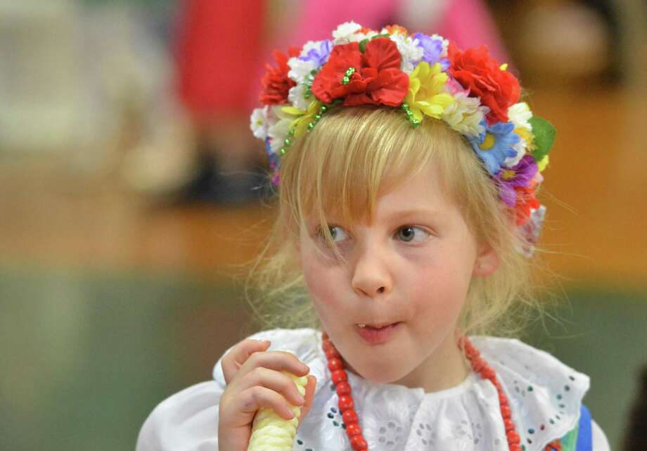 All Saints Catholic School 1st-grader Maya Witczak is dressed in her traditional polish dress and enjoys a treat from Slovakia called Tiger Sticks during All saints Catholic School International Night. More thatn 30 countries were represented with food and native clothing along with dance to bring awareness to the many cultures represented at the school on Wednesday April 25, 2018 in Norwalk Conn Photo: Alex Von Kleydorff / Hearst Connecticut Media / Norwalk Hour