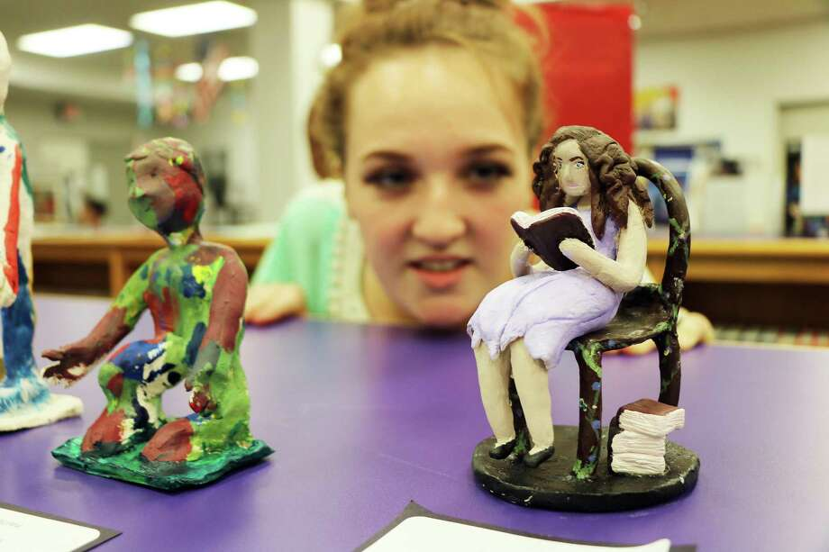 Dayton senior Breanna Brightwell gets a close look at her ceramic sculpture, which was a self-portrait. The Art II student loves to read and included a stack of books at her side. Photo: David Taylor / HCN