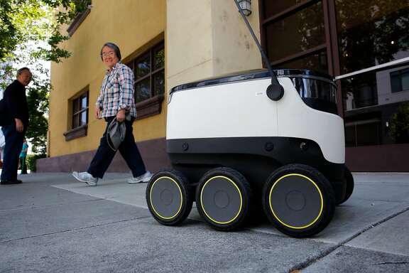 One of the food delivery robots of Starship Technologies draws looks from passersby during a delivery in downtown Redwood City, Ca., on Tuesday July 18, 2017.