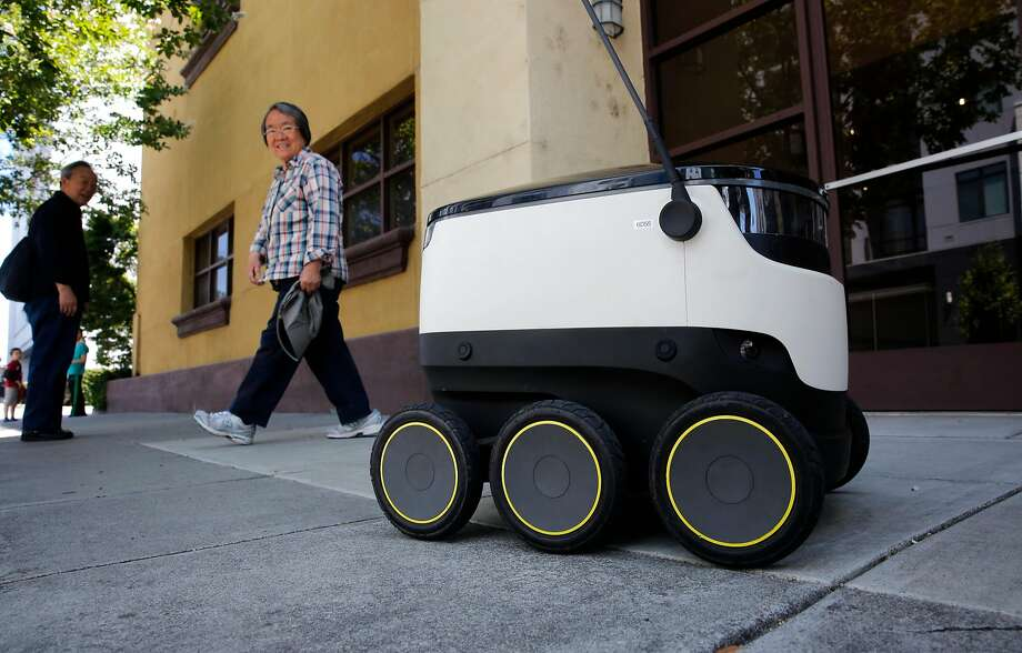 A food delivery robot from Starship Technologies draws looks from passersby during a delivery in downtown Redwood City. Photo: Michael Macor / The Chronicle 2017