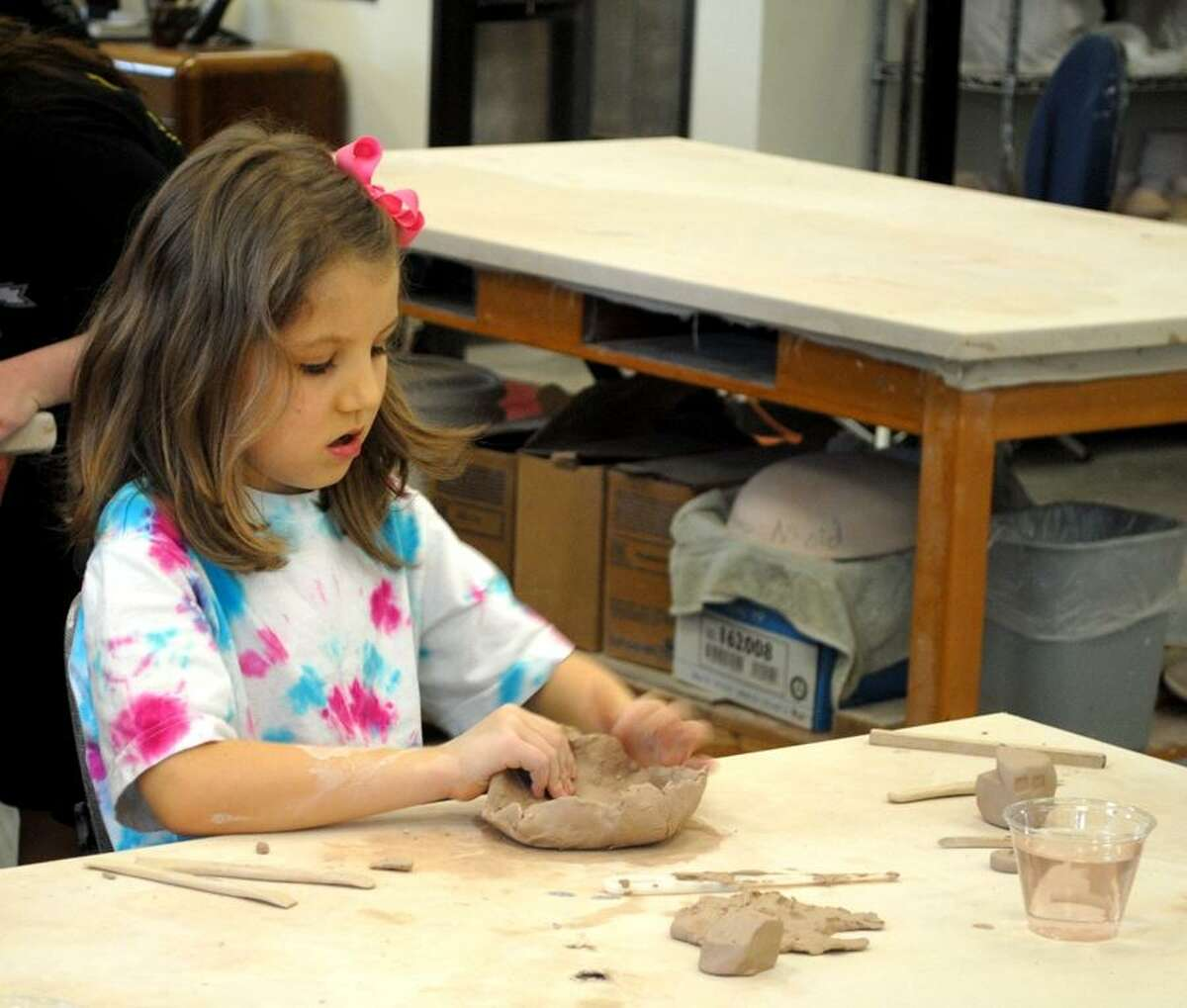 Pearland Homeschool Alliance student Grace Thomas, 7, of Pearland tries to make a bowl on Friday, February 24 at the Alvin Community College art building.
