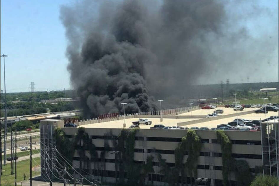 A column of thick smoke rises from a UH parking garage where officials say at least 11 vehicles caught fire, Thursday afternoon. Image courtesy of  @RoPennin