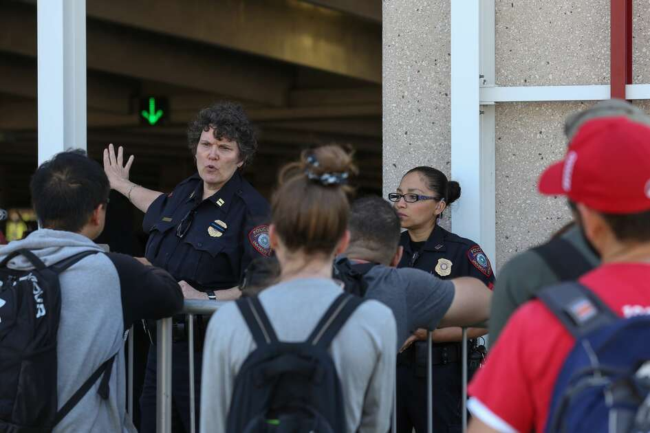 A University of Houston Police officer talks to students who are waiting to retrieve their vehicles after the Houston Fire Department extinguished a fire at the East Parking Garage Wednesday, April 25, 2018, in Houston. ( Godofredo A. Vasquez / Houston Chronicle )