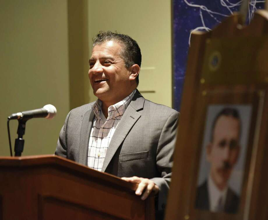 Greenwich High School Resource Officer Carlos Franco accepts his award beside a portrait of John A. Clarke during the annual John A. Clarke Awards Luncheon at the Hyatt Regency in Old Greenwich, Conn. Thursday, April 26, 2018. Presented on behalf of the Lions Club of Greenwich, the annual award is given to a member or members of the Greenwich Police Department to recognize oustanding achievements in the line of duty. This year's award was given to Greenwich High School Resource Officer Carlos Franco, who will be leaving after an 11 year tenure as the school's first Resource Officer. Officer Franco will be the commencement speaker at GHS's 2018 graduation ceremony. Photo: Tyler Sizemore / Hearst Connecticut Media / Greenwich Time