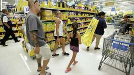 In this Tuesday, July 25, 2017 photo, Mark Spahr, left, is helped by employee Tiana Gerron, right, as he shops for school supplies with his daughters, Illeana Spahr, a sixth grader, and Elyse Spahr,  a third grader, at Walmart in Tomball, Texas. Walmart Back-to-School Helpers wearing super hero capes are stationed in the aisles to help customers. (Melissa Phillip/Houston Chronicle via AP)