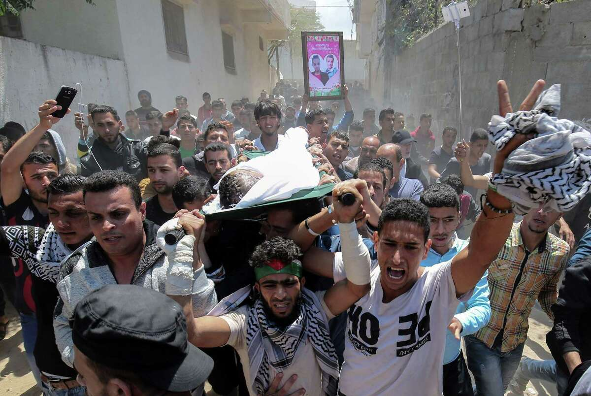 Mourners carry the body of Palestinian Tahrir Wahada, 18, during his funeral in Khan Yunis, in the southern Gaza Strip Monday. Wahada was wounded with a shot in the head by Israeli fire in a clash east of Khan Yunis on April 6 and was pronounced dead later.
