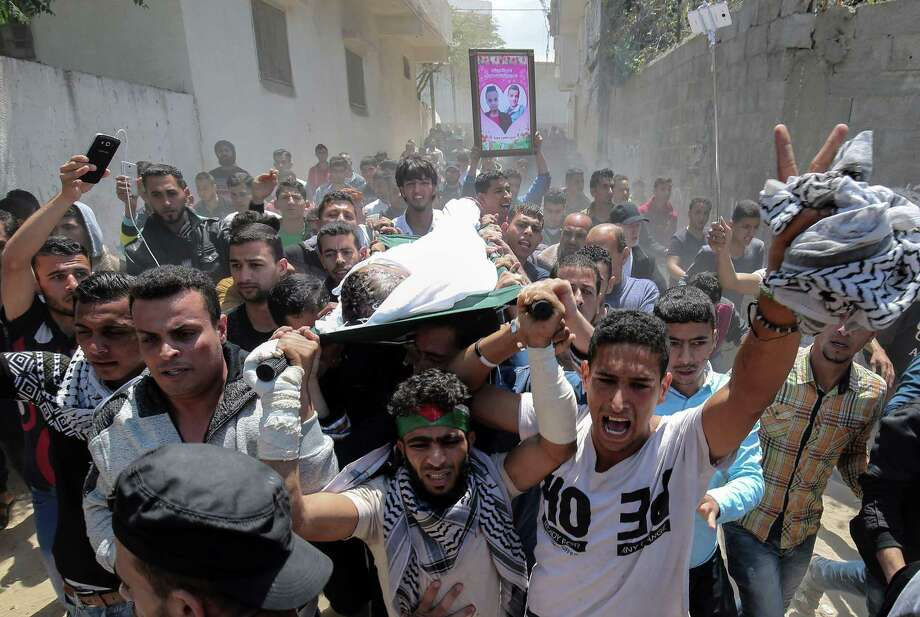 Mourners carry the body of Palestinian Tahrir Wahada, 18, during his funeral in Khan Yunis, in the southern Gaza Strip Monday. Wahada was wounded with a shot in the head by Israeli fire in a clash east of Khan Yunis on April 6 and was pronounced dead later. Photo: SAID KHATIB /AFP /Getty Images / AFP or licensors
