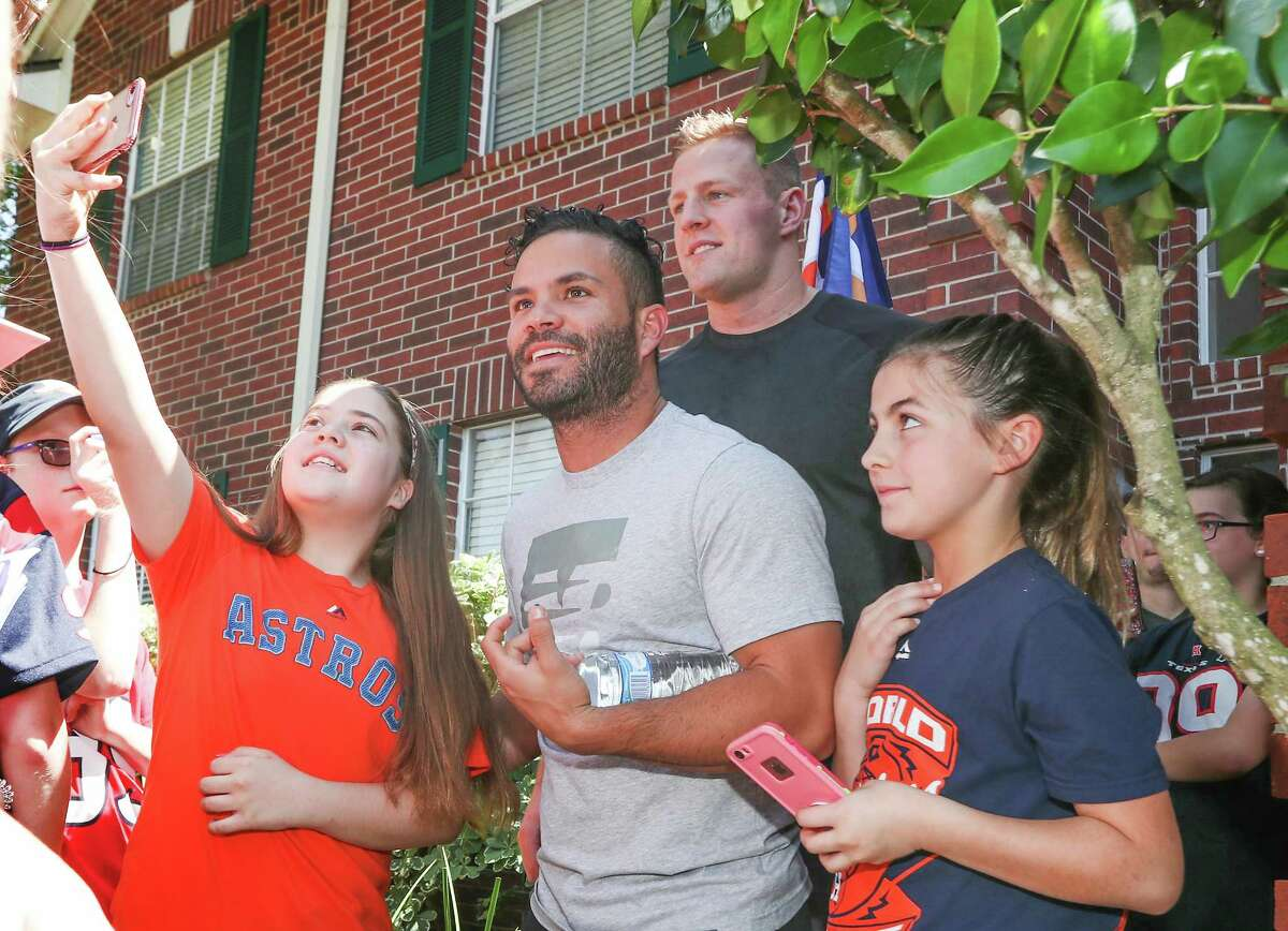 Houston Astros Jose Altuve and Houston Texans J.J. Watt pose for photos with a fans after they delivered a brand new Papa John's Pizza decorated truck to Donald Hayes Thursday, April 26, 2018, in Pearland. Hayes won the truck through a Papa John's Pizza contest.