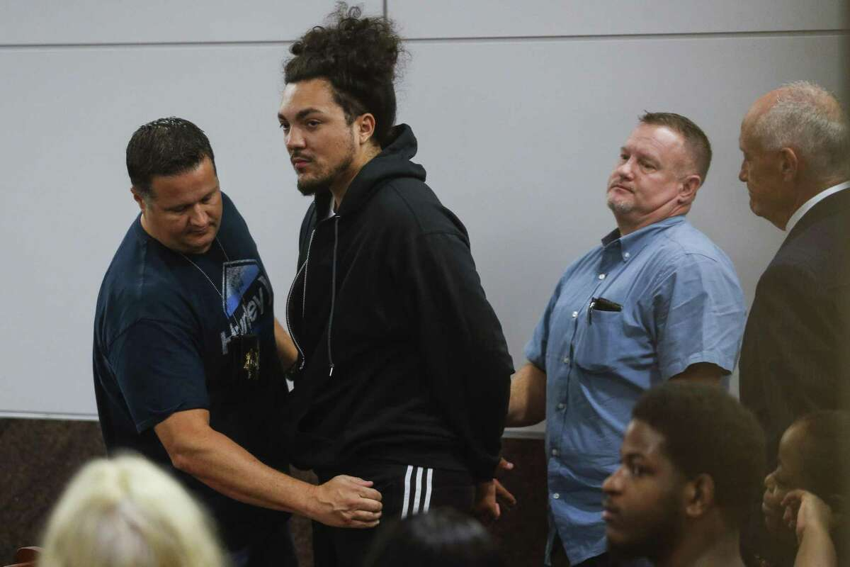 Police officers search Michael Anthony Cuellar, 29, in the 351st court at the Harris County Juvenile Courthouse before leading him out to a police car after he turned himself in after being identified as one of the shooters in a now-viral Snapchat video Tuesday, Oct. 3, 2017 in Houston. The video allegedly showed Cuellar and a passenger, Sierra Tarbutton, shooting from a car near the 15800 block of Memorial Drive. ( Michael Ciaglo / Houston Chronicle)