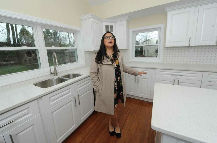 Gabby Villacis with Modern Day Real Estate shows the home at 4 Chelene Road for sale at $469,000 Wednesday, April 25, 2018, in Norwalk, Conn. The newly renovated cape has all new mechanicals, new kitchen and baths and has a square footage of 1700 feet. Photo: Erik Trautmann / Hearst Connecticut Media / Norwalk Hour