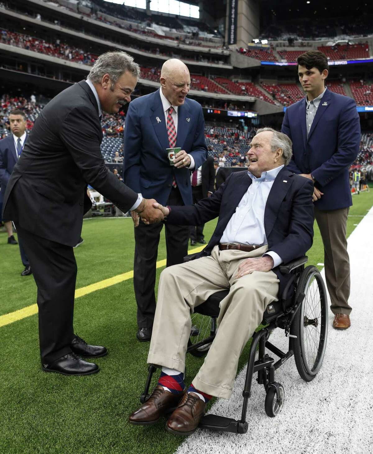 Houston Texans' COO Cal McNair, left, and owner Bob McNair greet former President George H.W. Bush before an NFL football game against the Indianapolis Colts at NRG Stadium on Nov. 5, 2017.