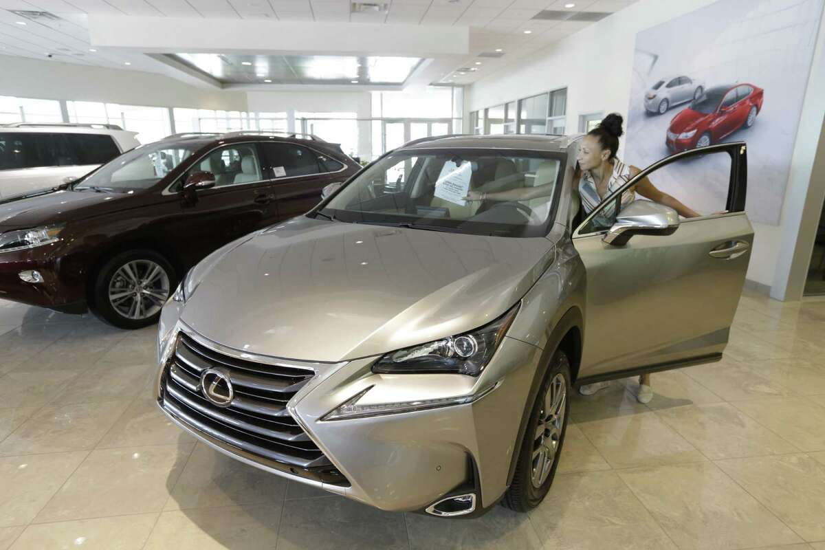 Lyza Postal, new car director, straightens a sales tag in a car at Sterling McCall Lexus, 10025 Soutwest Fwy., Thursday, July 23, 2015, in Houston. Group 1 Automotive, Inc., posted its highest quarterly earnings for the three months ending on June 30. ( Melissa Phillip / Houston Chronicle )