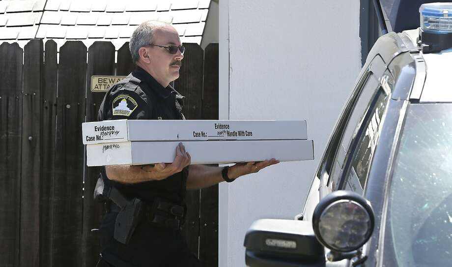 John Lopes of the Sheriff's Depart ment carries boxes of evidence. Photo: Rich Pedroncelli / Associated Press