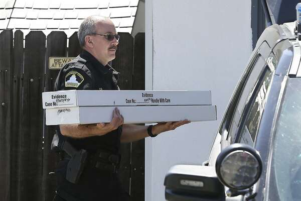 John Lopes, a crime scene investigator for the Sacramento Sheriff's office, carries boxes of evidence taken from the home of murder suspect Joseph DeAngelo to a sheriff's vehicle Thursday, April 26, 2018, in Citrus Heights, Calif. DeAngelo, 72, was taken into custody, Tuesday, on suspicion of committing multiple homicides and rapes in the 1970's and 1980's in California. Authorities spent the day going through the home for evidence. (AP Photo/Rich Pedroncelli)