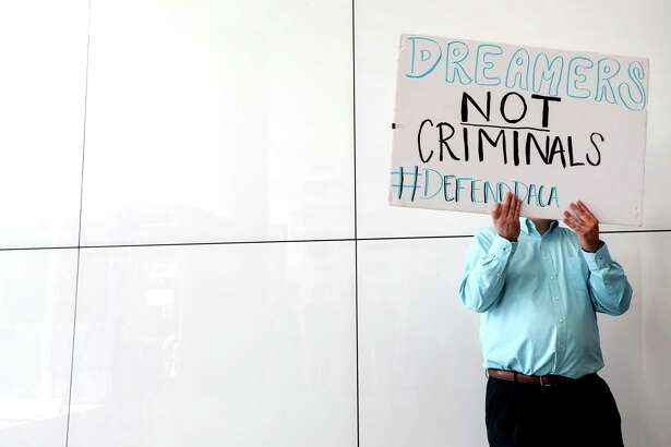 A man holds a sign during a 2017 press conference at the Mickey Leland Federal Building in Houston calling for action to help DACA recipients.