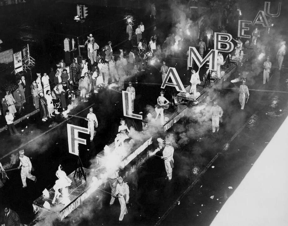 What appear to be torch-carrying ROTC cadets escort the Flambeau Parade's signature entry in 1956. Photo: File Photo / Express-News