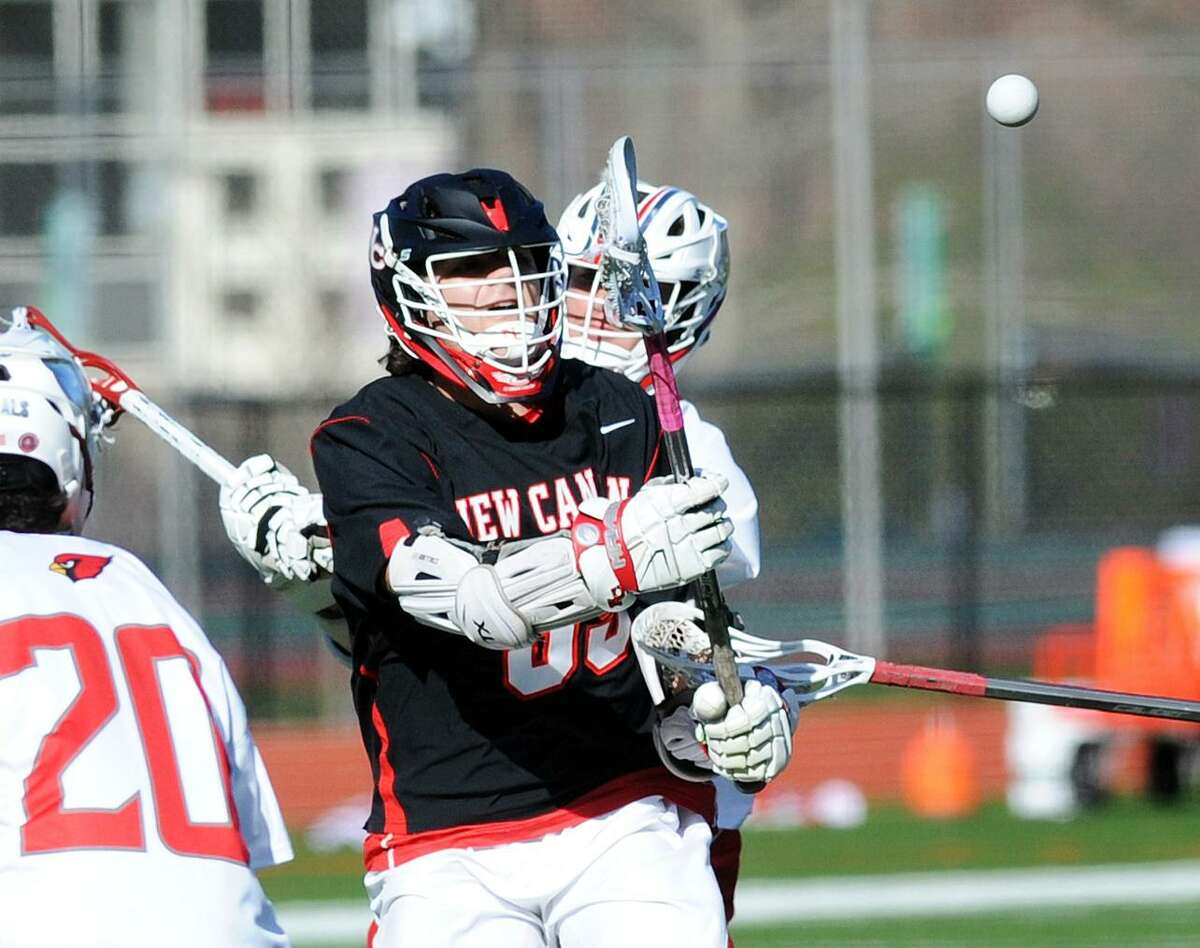 At right, Nicholas Crovatto of New Canaan passes as Sam Jenkins (#20) of Greenwich defends during the boys high school lacrosse match between Greenwich High School and New Canaan High School at Greenwich, Conn., Thursday, April 26, 2018.