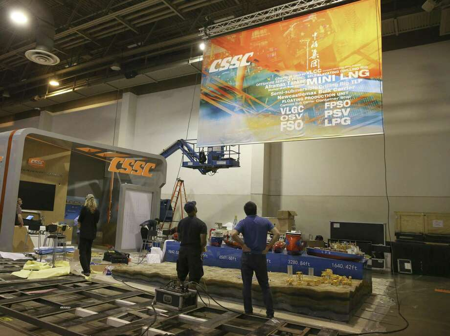 China State Shipbuilding Corporation staff watch their banner being set up for next week's Offshore Technology Conference at NRG Center on Thursday, April 26, 2018, in Houston. The 50th OTC show will run from April 30 to May 3. ( Yi-Chin Lee / Houston Chronicle ) Photo: Yi-Chin Lee / Houston Chronicle / © 2018 Houston Chronicle