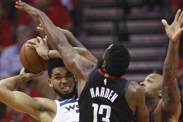 Minnesota Timberwolves center Karl-Anthony Towns (32) is cornered by Houston Rockets guard James Harden (13) and forward PJ Tucker during the first half of Game 5 of an NBA basketball first-round playoff series Wednesday, April 25, 2018, in Houston. (Brett Coomer/Houston Chronicle via AP)