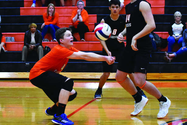 Edwardsville's Max Sellers successfully receives a serve during the second game of Edwardsville's match against Belleville East on Thursday.