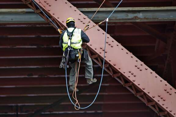 A bridge inspector grapples on to the Golden Gate Bridge checking for cracking of seismic damage in San Francisco, California, on Wednesday, July 8, 2015.
