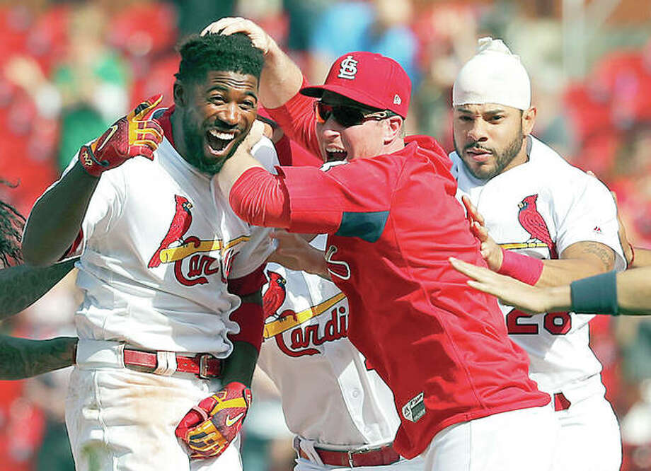 The Cardinals' Dexter Fowler, left, is congratulated by teammates Jedd Gyorko and Tommy Pham, right, after hitting a walkoff single in the 13th inning of Thursday's win over the Mets at Busch Stadium. Photo:     Jeff Roberson | AP Photo