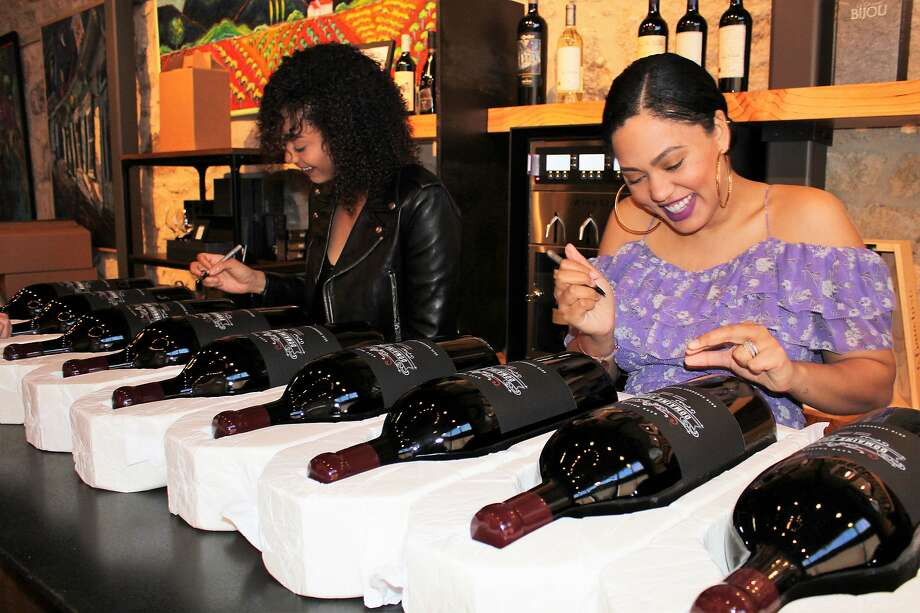 Sydel Curry (left) and Ayesha Curry, the sister and wife of Warriors player Stephen Curry, sign bottles of their new wine, a 2015 Napa Valley Cabernet Sauvignon called Femme 31 Photo: Naomi Filipelli