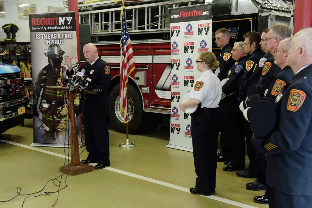 Tom With, left, FASNY assistant sergeant-at-arms for the board of directors, addresses those gathered during an event to announce the eighth annual RecruitNY statewide firefighter recruitment initiative at the Fuller Road Fire Department on Thursday, April 26, 2018, in Colonie, N.Y. (Paul Buckowski/Times Union)