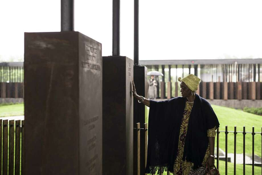 """MONTGOMERY, AL - APRIL 26: Wretha Hudson, 73, discovers a marker commemorating lynchings in Lee County, Texas while visiting the National Memorial For Peace And Justice on April 26, 2018 in Montgomery, Alabama. Hudson, whose father's family came to Alabama from Lee County decades earlier, said the experience was overwhelming. """"It's a combination of pride and strength, for my people. In our culture, rain is a sign of acceptance from our ancestors. So the rain is a sign of their acceptance for this day."""" The memorial is dedicated to the legacy of enslaved black people and those terrorized by lynching and Jim Crow segregation in America. Conceived by the Equal Justice Initiative, the physical environment is intended to foster reflection on America's history of racial inequality. (Photo by Bob Miller/Getty Images) Photo: Bob Miller / 2018 Getty Images"""
