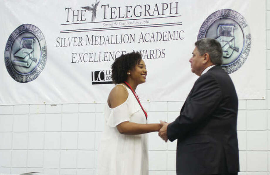 Alton High School senior Anya Jones is congratulated by Alton School District Superintendent Mark Cappel during the 30th annual Silver Medallion Academic Excellence Awards Banquet, held Thursday at Lewis and Clark College. The event honors the top eight percent of students from 21 local high schools. Photo:       Scott Cousins | The Telegraph