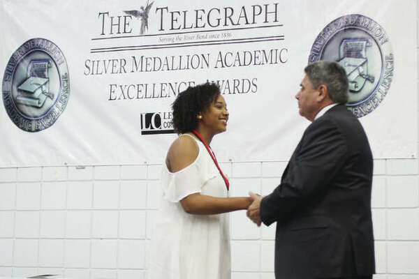 Alton High School senior Anya Jones is congratulated by Alton School District Superintendent Mark Cappel during the 30th annual Silver Medallion Academic Excellence Awards Banquet, held Thursday at Lewis and Clark College. The event honors the top eight percent of students from 21 local high schools.