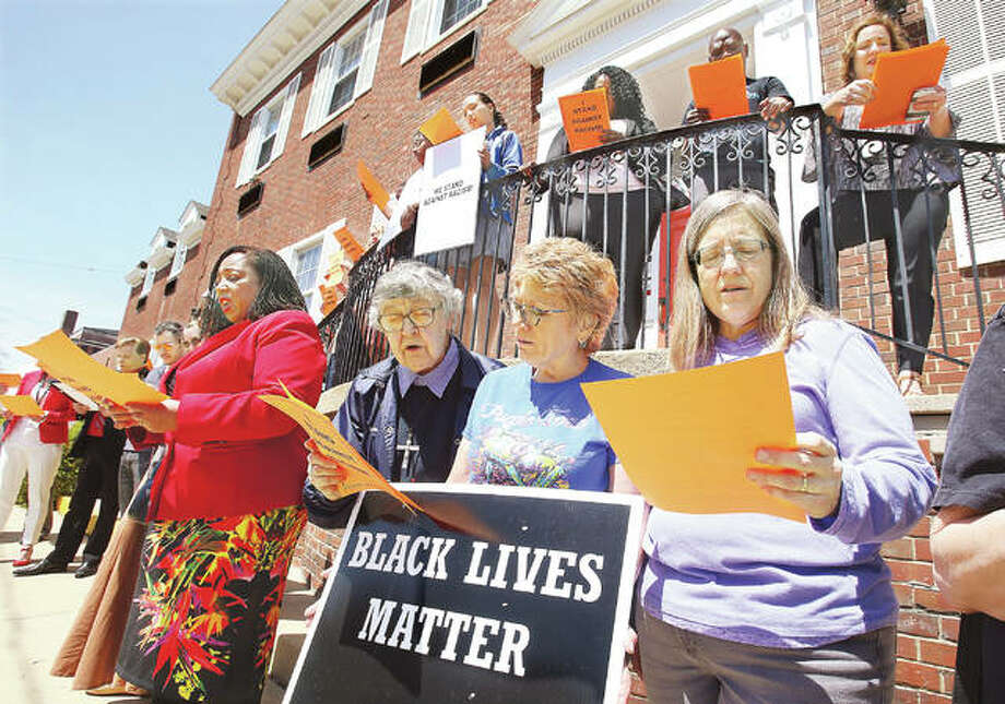 """Some of a group of almost 40 people, who attended a stand against racism event Thursday at the Alton YWCA, read a pledge to work to eliminate racism in all of its forms, outside the building on E. Third Street. Alton Mayor Brant Walker also read a proclamation declaring Thursday through the Sunday as """"YWCA Stand Against Racism Weekend"""". Photo:       John Badman 
