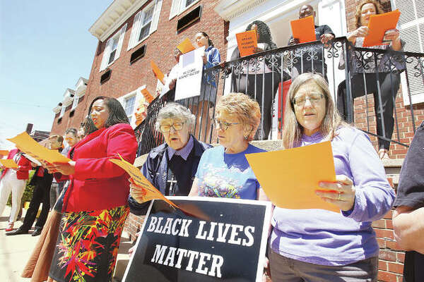 "Some of a group of almost 40 people, who attended a stand against racism event Thursday at the Alton YWCA, read a pledge to work to eliminate racism in all of its forms, outside the building on E. Third Street. Alton Mayor Brant Walker also read a proclamation declaring Thursday through the Sunday as ""YWCA Stand Against Racism Weekend""."