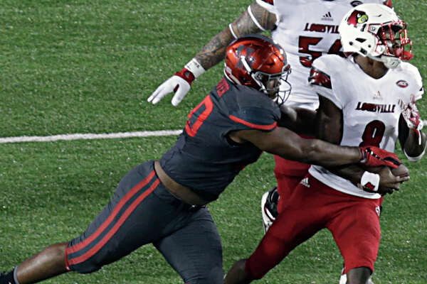 University of Houston defensive tackle Ed Oliver left, sacks Louisville Cardinals quarterback Lamar Jackson during the second half of college football game action at TDECU Stadium Nov. 17, 2016, in Houston. ( James Nielsen / Houston Chronicle )