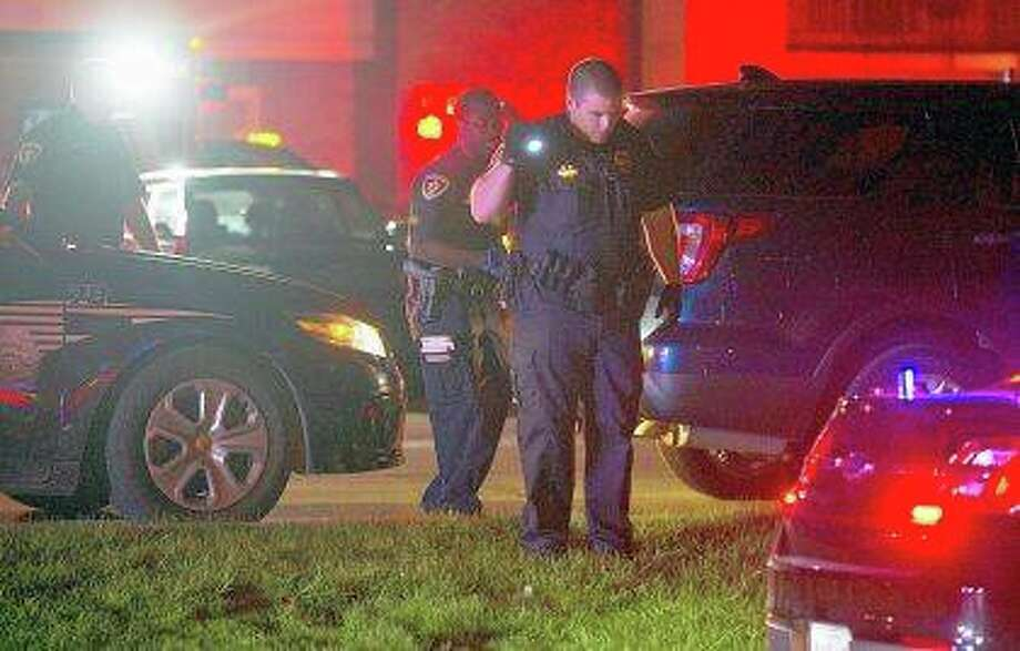 Police in Normal search for evidence following a shooting at an apartment complex where two men were found dead. Photo:       Lewis Marien | The Pantagraph (AP)