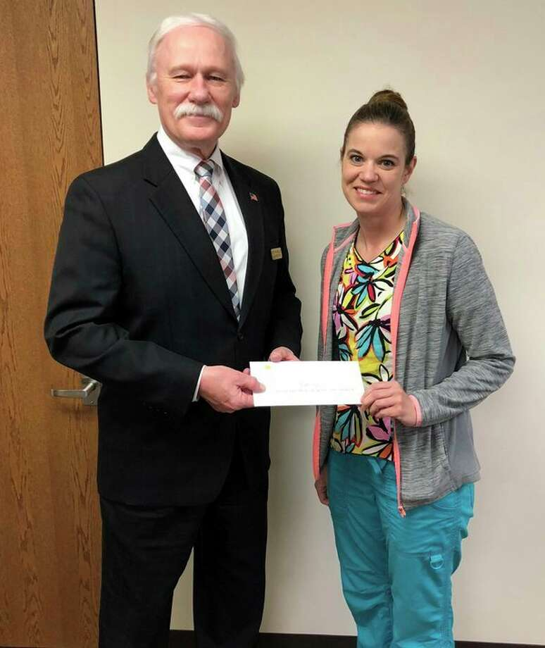 Renee Guza, a certified nursing assistant, recently accepted a Michigan County Medical Care Facilities Council Scholarship Endowment from Keith Miller, Huron County Medical Care Facility Administrator. Guza has been working at the facility while pursuing her educational goal at Baker College of becoming a registered murse. Miller said the company is proud to see Guza honored for her academic achievements. (Submitted photo)