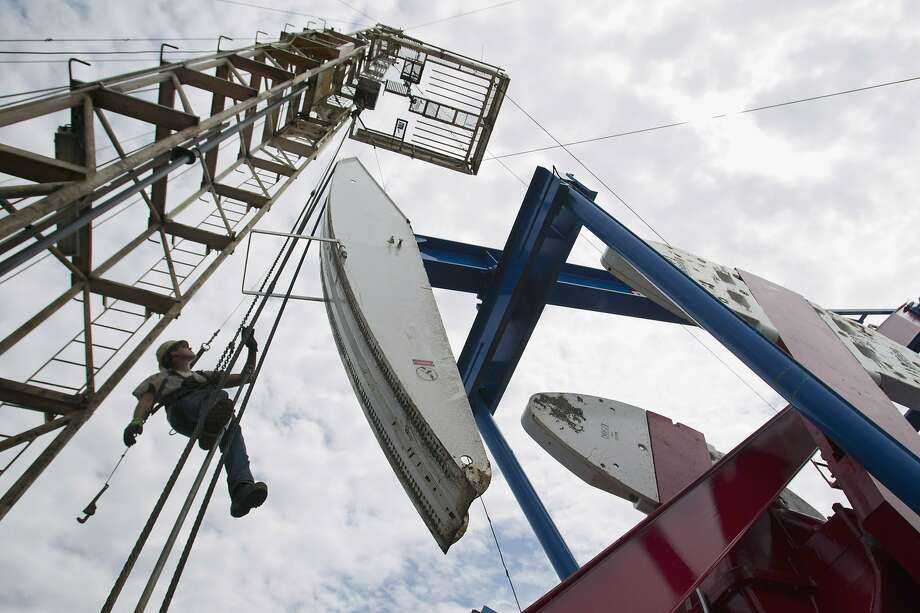 FILE - In this July 26, 2011, file photo, a worker hangs from an oil derrick outside of Williston, N.D. State data show that 1 billion barrels of oil have been produced from the rich Bakken shale formation in western North Dakota and eastern Montana. Data show that North Dakota has tallied 852 million barrels of Bakken crude, and Montana has produced about 151 million barrels. (AP Photo/Gregory Bull, File) Photo: Gregory Bull, ASSOCIATED PRESS